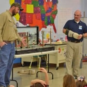 Material Handler Alan Carter, left, and Energy Specialist Nathan Wagner, right, show students how to be safe around electric lines and equipment.